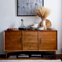 "$899 Simple and sophisticated. The Mid-Century Buffet's beveled edges, warm acorn color and bronze-finish hardware celebrate the timeless style of 1950s and '60s modernism. Fitted with three drawers and a cabinet with a shelf, it's versatile enough to house your dinnerware and flatware collections while also being a perfect perch for your flatscreen. 57""w x 19""d x 30""h."