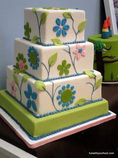 Great cake for a spring wedding, love the cute little gnome topper couple on the other cake next to it.