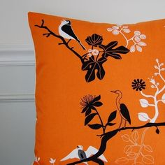 The birds on this pillow can soften the edginess of a burnt orange and black color scheme.