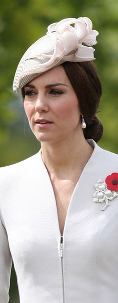 Catherine, Duchess of Cambridge accessorized with a delicate grey and pink hat and pearl drop earrings, during her visit to the Commonwealth War Graves Commission Cemetery Bedford House on the outskirts of Ypres, Belgium