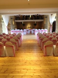Coral pink organza sashes on white chair covers with aisle side sashes with diamanté buckles