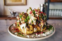 Roasted cauliflower, homemade tahina, and spicy parsley sauce will make you forget this dish is vegetarian.