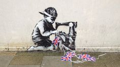Union Tat: Graffiti artist Banksy is believed to be behind a new painting which shows a boy hunched over a sewing machine stitching union flag bunting.