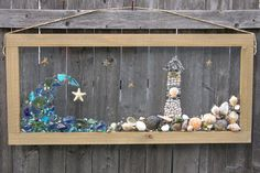 Lighthouse & Wave features Sea glass, Beach Glass, Sea shells and Starfish. Handmade wood 14 3/4 X 32 3/4 Wood Frame. Makes a gorgeous showpiece in a bay window. Great gift idea. All products are handmade no two items are the same. Each item is carefully designed and sealed in an UV epoxy resin.The frames are all handcrafted and stained. All products come with hardware installed to be hung.