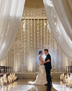 Indoor Wedding Ceremony ~Elegant Arch Decorations Created out of hanging flower cascade in graduated lengths. . Fantastic Inspiration!