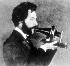 Alexander Bell using the first telephone he invented.