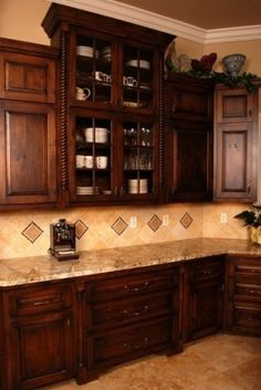 dark cabinets and tiled walls. barley twist detail on cabinets. Like the colors. Not sure about the dark tile in the backsplash.
