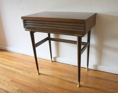 This is a mid century modern vanity console table with a louvered drawer and brass tipped legs and brass accents. Perfectly compact for entryways, a bedroom vanity, or a taller side table. Dimens…