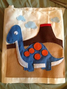 Dinosaur quiet book page. The spots velcro on and off and the volcano is a pocket.