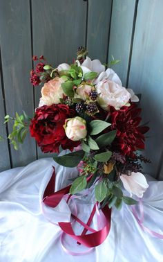 If you are interested in purchasing multiple items please sent me a convo for a custom listing for saving on shipping costs. Cacasding boho bouquet in marsala burgundy and blush. Peonies and real touch buds, magnolias and cabbage roses with seeded eucalyptus. Matching corsage,