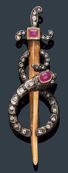 AN ANTIQUE GARNET AND DIAMOND BAR BROOCH, France, ca. 1880. Silver and pink gold. Decorative brooch designed as a golden sword with an entwined snake. The handle set with one square-cut garnet and 10 rose-cut diamonds, the snake in silver, set with one oval garnet and 24 small rose-cut diamonds. #antique #BarBrooch