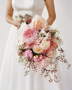 "A combination of flowers large (peonies and ranunculus), medium (sweet peas), and petite (jasmine and 'Hally Jolivette' cherry blossoms) gives this bouquet dimension. Silk organza ""Ennise"" dress, Rivini."