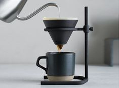 The brewer stand set intrigues with its rough look. It comes with a brewer stand made by casting, porcelain brewer, paper filters, server, a. Coffee Brewer, Coffee Cups, Coffee Maker, Coffee Set, Cafetiere Design, Coffee Facts, Coffee Equipment, Coffee Dripper, Coffee Stands