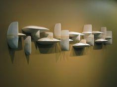 maren kloppmann - hangende keramiek die a.h.w. achter de muur door gaat. Het kan een half gezicht of een halve figuur zijn.