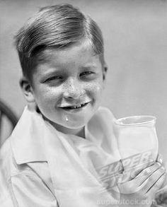 1930s, boy drinking a glass of milk