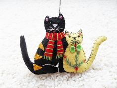 """This ornament features two cats sitting side by side. One is wearing a red scarf, the other is wearing a cute three-dimensional bow-tie. Nothing can be more cute than this couple! If your a cats lover, then this will definitely warm your heart right up!    The cats are embroidered with seed beads and is blanket stitched around the edges. It is stuffed with poly fibrefill. Comes with an ornament string at the top. Size: 3.5""""  Price: $9.70"""