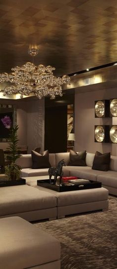 Wallpaper in ceiling , with elegant chandelier and deep muted shades on wall, creates a classy mood in the living space.