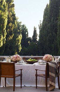 A breathtakingly romantic outdoor table setting for two with a magnificent garden vista