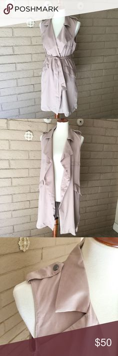 "Romeo & Juliet Trench Vest Romeo & Juliet Trench Vest in Khaki ""Sand"" Color Great closet staple! Can be worn as a vest or tied as a dress. Draped front, pockets, waist tie and snap button shoulder detail Size M Brand new with tags attached! Romeo & Juliet Couture Jackets & Coats Vests"
