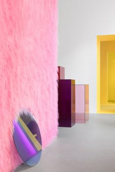 Circular, rectangular and irregular mirrors on the floors and walls reflect the neon pink fluff, green plant fronds and custom furniture, which includes display podiums made from translucent coloured glass.