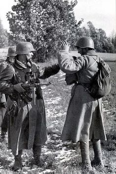 German NCO inspecting a recently captured Soviet soldier. Note the foot wraps on the Soviet.