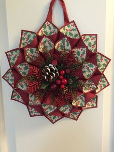 Red paper cone wreath. Each cone has holly berry paper on the inside. Centered with a holiday pine cone floral with red glittery accents.