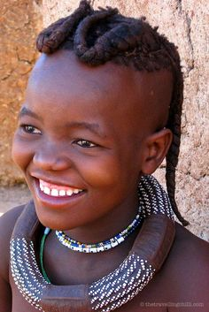 The Himba people are a tribe in Namibia - They live according to traditional beliefs and culture - Beautiful smiling Himba girl
