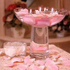 Precioso centro de mesa con petalos de rosa y velas.