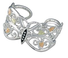Landstrom's Black Hills Gold This elegant sterling silver cuff bracelet is a delicate butterfly enhanced by classic Black Hills Gold styling: 12K rose and green leaves. Jewelry is 10K gold or sterling