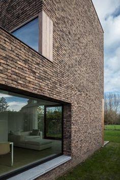 Bakstenen contrasteren met de strakke vorm van de woning. -- Caan Architecten - halfopen woning in Hansbeke
