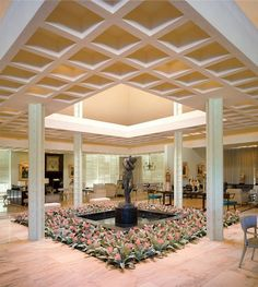 Rodin's bronze Eve, surrounded by a bed of bromeliads, in the center of the combination entrance atrium and living room.