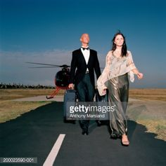 Stock Photo : Woman walking away from helicopter, butler following carrying cases