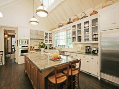 cococozy+hamptons+house+kitchen+a+frame+high+ceiling+rustic+wood+floors+white+cabinets+glass+upper+cabinetry+island+granite+counters.jpg 800×600 pixels