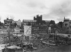 Signboards advertising new locations of shops that once stood on Exeter High Street before their demolition following the Blitz on the city in April and May 1942. Exeter Cathedral, Exeter Devon, The Blitz, World War Ii, New York Skyline, Wolf, Advertising, Shops, England