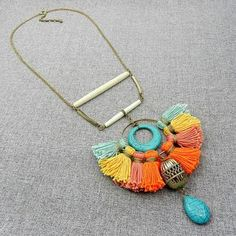 Bright multicolored bohemian tassel statement bib necklace with bone, stone and metal elements. One of my personal favorites, this boho tassel bib is all you need to accessorize your day look and get noticed ! Needless to say, its bright colors will liven up your day! The focal unit of this rather eclectic necklace is made up of several handmade pure cotton tassels in vibrant colors, howlite turquoise stone beads, a large dull gold plated metal filigree bead, dull gold plated brass tubes…
