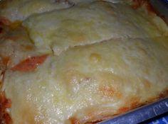 Receita de Lasanha com a Massa de Panqueca de Presunto e Mussarela - margarina para untar, pimenta do reino, sal, 2 ovos, 2 xícaras (chá) leite, 2 xícaras (chá) farinha de trigo, 1 dente de alho picado, 1 caixinha de creme de leite 200 ml, 1/2 cebola picada, 1/2 litro de molho de tomate, , 200 gramas de presunto fatiado, 500 gramas de muçarela fatiada, 200 gramas de queijo parmesão ralado