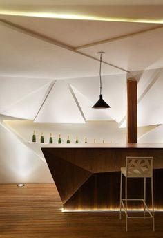 meuble bar design en bois de sucupira, avec un éclairage indirect et suspension noire devant le mur facetté blanc