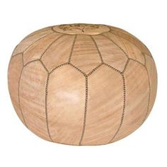 Showcasing a Moroccan-inspired arch motif and tan hue, this handmade faux leather pouf is perfect as an extra seat or an exotic footrest.