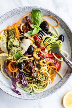 Pesto Zoodles / This Italian Pesto zoodle salad is topped with tons of flavor from roasted peppers, artichoke hearts, olives, and sun dried tomatoes, and drizzled with a Pesto vinaigrette. | SUNKISSEDKITCHEN.COM | #pesto #zoodles #zoodlesalad #salad #Italian #artichokehearts #olives #sundriedtomatoes #basil