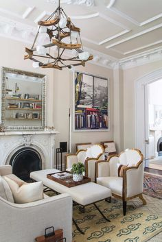 """The living room has a working fireplace (the others are now only decorative). """"I have been using it all winter,"""" Roeder says. She painted the walls here using Benjamin Moore AF-65 and found the club chairs on eBay from an antiques dealer in Hungary. She later reupholstered them. The large sisal rug was custom cut from A-1 Interior Carpets on the Upper East Side, and the kilim is from Roeder's parents. The area rug in front of the fireplace is from an antiques store in London."""