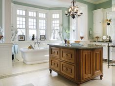 This bath creates a luxurious space for a couple. A freestanding quarter-sawn island centered in the room matches the quartered oak double doors and offers continuity moving into the room. Each spouse has his or her own space with two large, white painted vanities, double medicine cabinets and framed mirrors. Design by Peter Ross Salerno