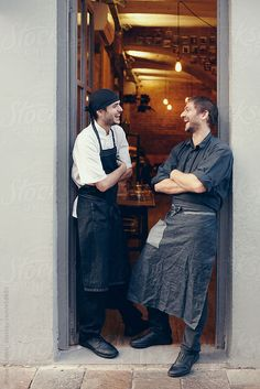 Two cooks laughing together at the door of the coffee shop by Miquel Llonch