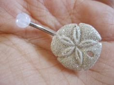 Glitter sand dollar belly ring (If I were to ever have a bikini ready body, a belly button piercing, and had the money to go to a beach, I'd wear this, lol - G)