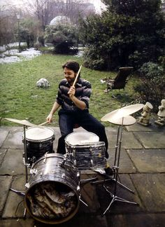 Paul McCartney  drumming at his simple drum kit outdoors on the garden patio.