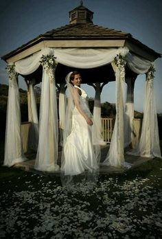 Here she is, my sister!!! My mother in law and I decorated the simple gazebo with white sheers that we cut, draped, poofed & stapled to soften the poles. Then added flowers for a truly romantic setting.