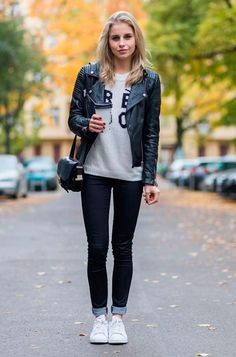 Street style look com jaqueta de couro preta, calça jeans e tênis.