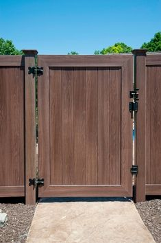 VWG300-46 Solid Tongue & Groove Walk Gate in Grand Illusions Vinyl Woodbond Walnut Grain (W103). Gate hardware includes CPH55 Corner Plate Hinges S.S., VGSH Gate Stop/Handle Combo, an additional VGS Gate Stop, and HLSS Hatchet Latch S.S. Installed with V300-6 6' T&G PVC Privacy Fence.