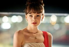 Hair pinned up with bright red lipstick, pearl earrings, spaghetti strapped dress