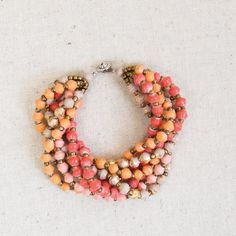 """HPNWT Sorbet & Gold Seven Strand Bracelet NWT.  Beautiful seven strand bead bracelet.  Pink, brick, tangerine, beige, and gold.  Approximately 8"""" long when laid flat.  Button clasp. Thirty One Bits Jewelry Bracelets"""
