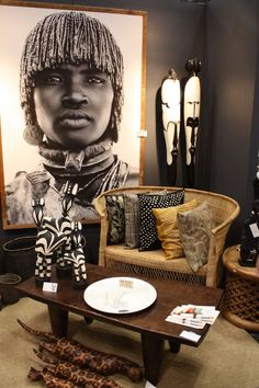 This striking living room exemplifies global style, and has many wonderful African tribal touches. The coffee table is wonderfully irregular with its hand-hewn legs.There are a lot of patterns, from the cushions to the abstracted zebras and leopards. I love those two huge masks: they are not the common ones you see. What an amazing portrait of an African woman in her tribal clothing, and I love how it is sepia toned. The dark bronze-brown walls set off all these natural colours.
